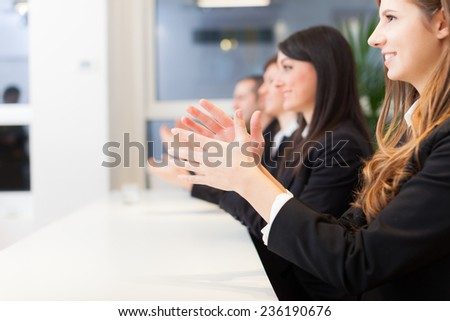 Group of happy business people applauding during a conference - stock photo