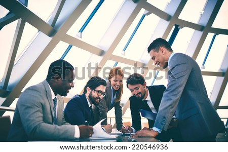 Group of happy business people discussing papers at meeting - stock photo