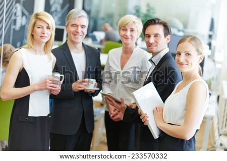 Group of happy business people standing in the office - stock photo