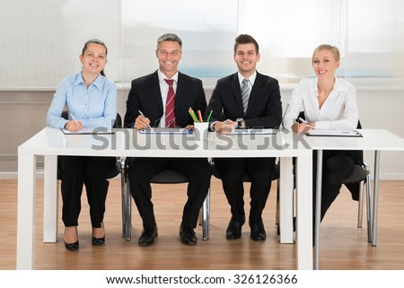 Group Of Happy Businesspeople Analyzing Graph At Desk - stock photo