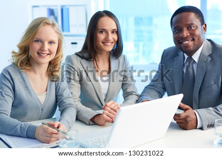 Group of happy businesspeople looking at camera with smiles - stock photo