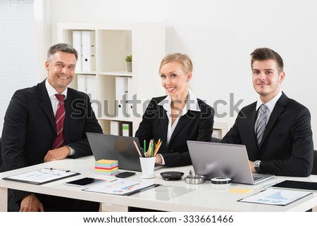 Group Of Happy Businesspeople Sitting At Desk - stock photo