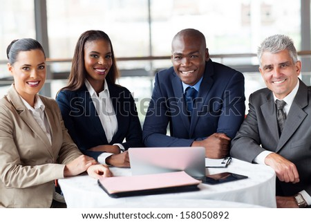 group of happy businesspeople sitting in office - stock photo