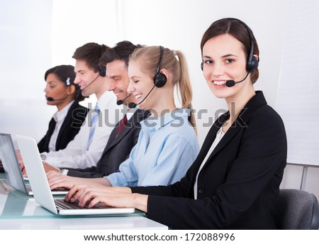 Group Of Happy Businesspeople Wearing Headset Working At Office Desk - stock photo