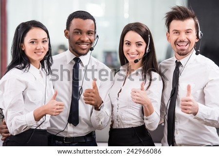 Group of happy, cheerful call center workers are smiling and looking at the camera.