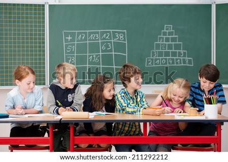 Group of happy children at work in the classroom sitting working on their projects at a long table in front of a blackboard - stock photo