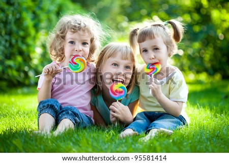 Group of happy children eating fruit drops outdoors in spring park - stock photo