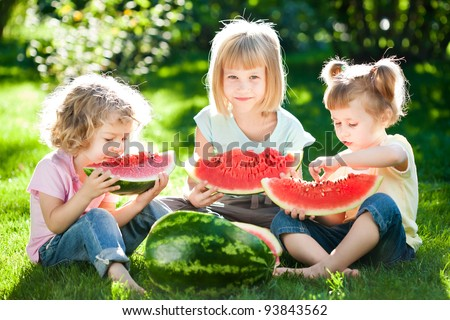 Group of happy children eating watermelon outdoors in spring park - stock photo