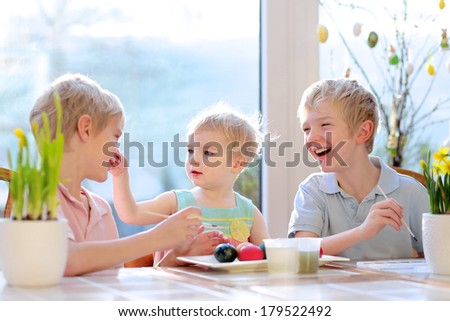 Group of happy children from one family, two twin brothers and their little toddler sister, decorating and painting Easter eggs sitting together in the kitchen on a sunny day. - stock photo