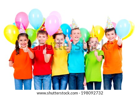 Group of happy children in colored t-shirts and party hats with balloons showing thumbs up sign on a white background.