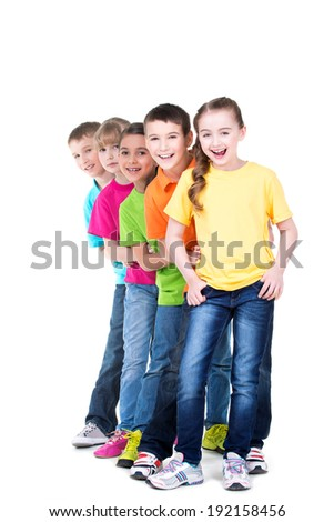 Group of happy children in colorful t-shirts stand behind each other on white background.