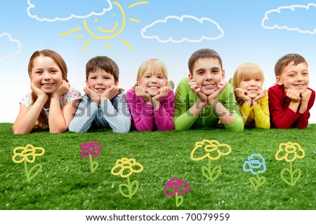 Group of happy children lying on a green grass - stock photo