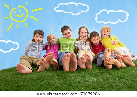 Group of happy children relaxing on the grass together - stock photo