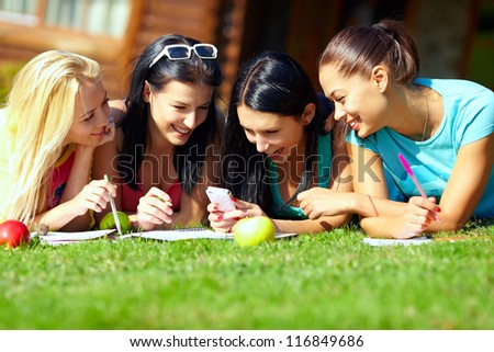 group of happy college girls chatting in social network on green lawn - stock photo