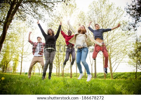 Group of Happy College Students Jumping at Park,Italy - stock photo
