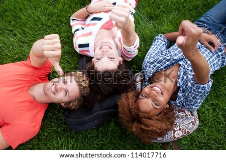 group of happy college students lying in the grass looking up - stock photo