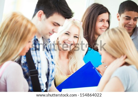 Group of happy college students standing together in the hallway. - stock photo