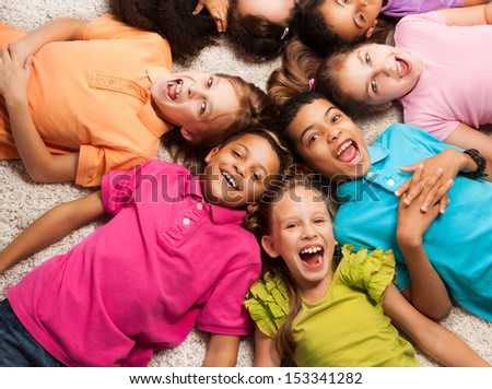 Group of happy diversity looking kids laying in star shape on the floor - stock photo