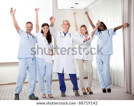 Group of happy doctors smiling and waving after a successful surgey at a hospital - stock photo