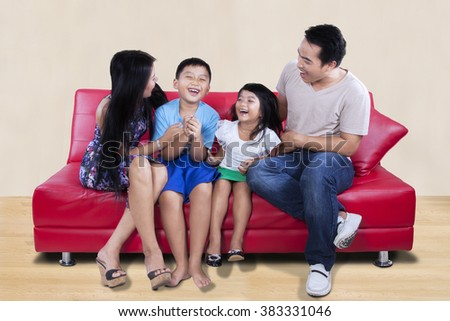 Group of happy family having fun together on the couch while sitting on the sofa and laughing together - stock photo