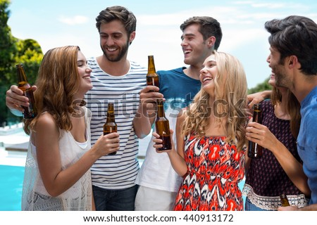 Group of happy friend holding beer bottles near pool - stock photo