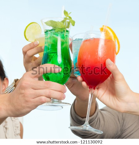 Group Of Happy Friends Celebrating Toasting With Glasses Of Cocktails - stock photo
