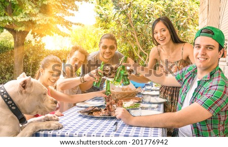 Group of happy friends eating and toasting at garden barbecue - Concept of happiness with young people at home enjoying food together - stock photo