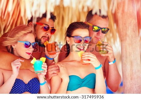 group of happy friends having fun on tropical beach, drinking colorful cocktails - stock photo