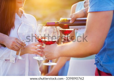 Group of happy friends having red wine on the beach. Sunset beach party - stock photo
