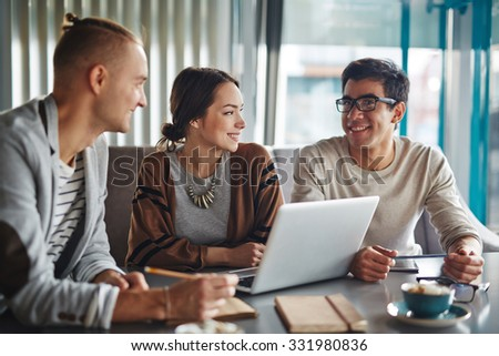 Group of happy friends or business people talking in office or cafe - stock photo