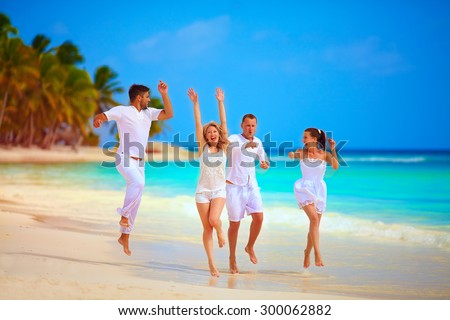 group of happy friends running on tropical beach, summer vacation - stock photo