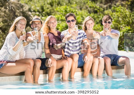 Group of happy friends sitting side by side at poolside with glass of champagne