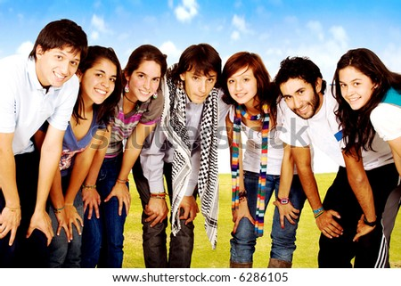 group of happy friends smiling for a portrait in a park with green grass and a blue sky in the background - stock photo