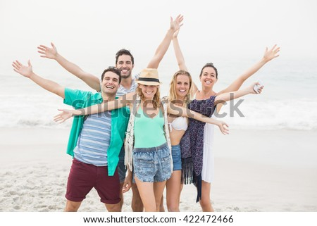 Group of happy friends standing on the beach with their arms outstretched - stock photo