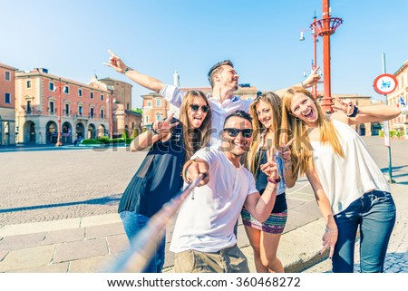 Group of happy friends taking a selfie with stick outdoors - Concept of young people having fun and using new communication technologies - stock photo
