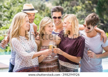Group of happy friends toasting champagne glasses near pool - stock photo