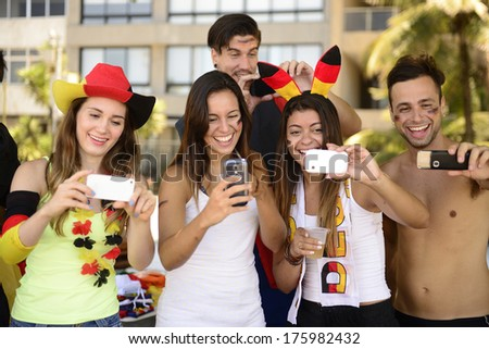 Group of happy German soccer fans holding smartphones - stock photo