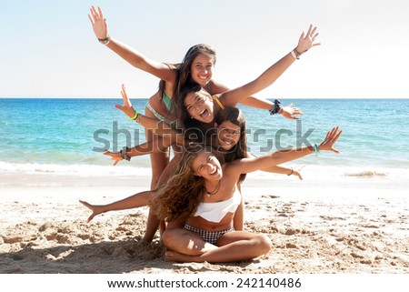 Group of happy girl teens at the beach - stock photo