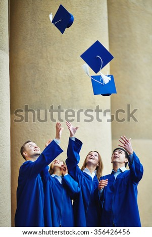 Group of happy graduates throwing their mortarboards upwards - stock photo