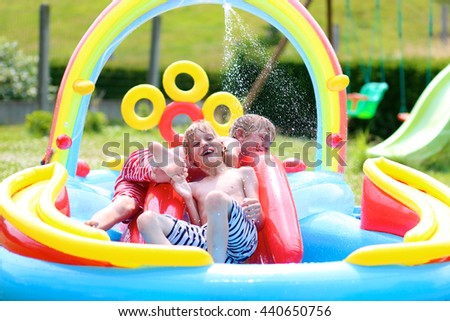 Group of happy healthy kids having fun in inflatable play centre. Children enjoying summer holidays playing in the pool at the backyard in the garden. - stock photo