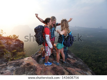 Group of happy hikers standing on top of a mountain