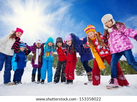 Group of happy kids, having fun on snow day, holding hands, laughing and smiling - stock photo