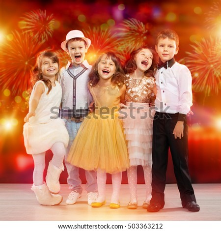 Group of happy kids in holiday clothes with fireworks on background. Holidays, christmas, new year, xmas, friendship, birthday, fashion concept.