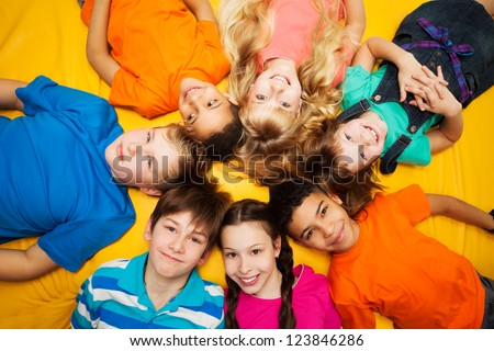 Group of happy kids laying in circle - diversity looking Caucasian and black boys and girls smilng - stock photo