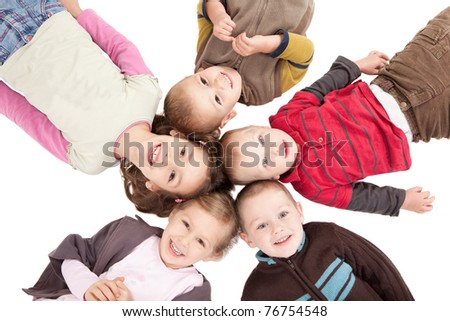 Group of happy kids lying on backs on isolated white floor. - stock photo