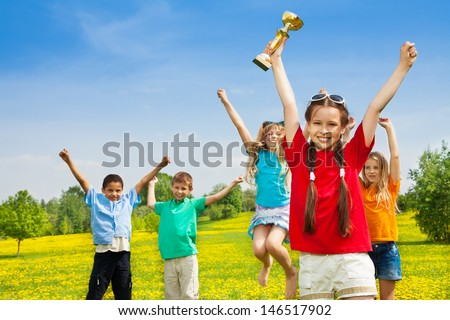 Group of happy kids of winner team with leader holding prize award cup - stock photo