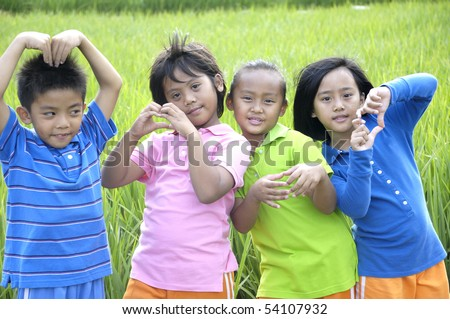 group of happy kids open hand in the green rice fields - stock photo