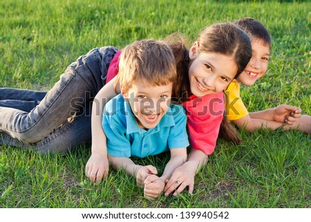 Group of happy kids playing on the green meadow - stock photo