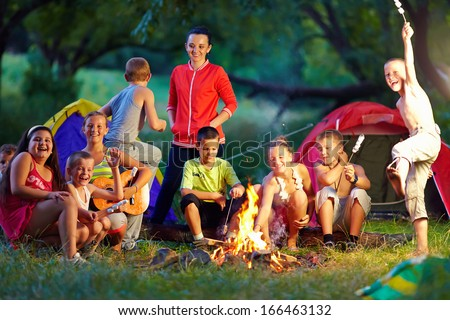 group of happy kids roasting marshmallows on camp fire