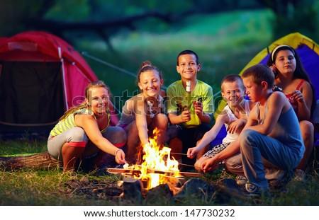 group of happy kids roasting marshmallows on campfire - stock photo